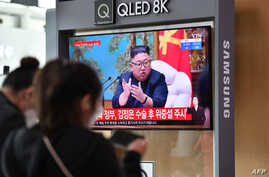 People watch a television news broadcast showing file footage of North Korean leader Kim Jong Un, at a railway station in Seoul…