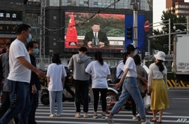 TOPSHOT - A news program shows Chinese President Xi Jinping speaking via video link to the World Health Assembly, on a giant…
