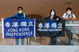 """People hold banners as they attend a """"Lunch With You"""" rally inside a shopping mall in the Central district of Hong Kong on June…"""