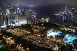 (FILES) This file photo taken on June 4, 2019 shows people attending a candlelight vigil at Victoria Park in Hong Kong, to mark…