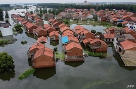 An aerial view shows flooded residential buildings due to rising water levels of the Yangtze river in Jiujiang, China's central…