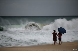 TOPSHOT - Two men watch the waves during swells brought by the approaching typhoon Maysak on Haeundae beach in Busan on September 2, 2020. - Flights were grounded in South Korea and storm warnings issued on both sides of the Korean peninsula as a…