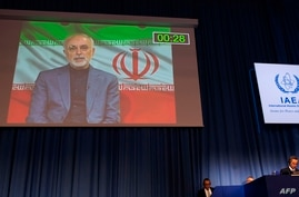 Rafael Grossi (R), Director General of the International Atomic Energy Agency (IAEA), listens to Mohammad Javad Zarif (L),…