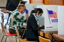 People vote inside City Hall on the first day of in-person early voting for the November 3rd elections in Kenosha, Wisconsin,…
