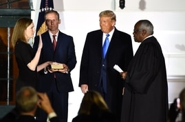 TOPSHOT - US President Donald Trump watches as Supreme Court Associate Justice Clarence Thomas (R) swears in Judge Amy Coney…