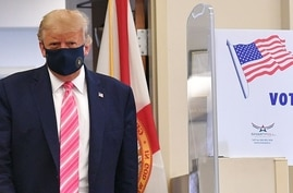 TOPSHOT - US President Donald Trump leaves the polling station after casting his ballot at the Palm Beach County Public Library…