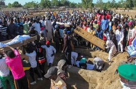 TOPSHOT - Mourners attend the funeral of 43 farm workers in Zabarmari, about 20km from Maiduguri, Nigeria, on November 29, 2020…