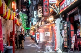 A couple (L) hugs along a street outside restaurants at Omoide Yokocho alleyway in Shinjuku district in Tokyo on January 7,…
