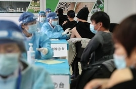 TOPSHOT - People receive vaccines against the Covid-19 coronavirus at a temporary vaccination centre in Beijing on January 8,…