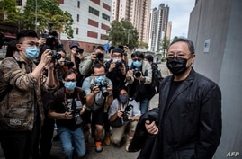 Hong Kong law professor and pro-democracy activist Benny Tai (R) arrives at Ma On Shan police station in Hong Kong on February…