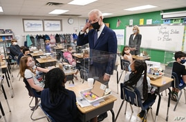 TOPSHOT - US President Joe Biden  points to his hair after a student told him she wanted to be a hairstylist when she grows up,…