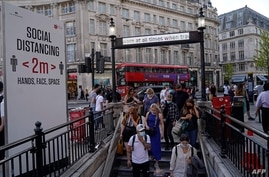 Commuters wearing face coverings due to Covid-19, enter Oxford Circus London Underground station in central London on June 7,…