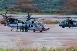 The Colombian presidential helicopter (L) sits at the tarmac of the Camilo Daza International Airport after being hit by…