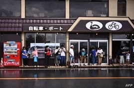 Spectators shelter from the rain during the men's cycling road race during the Tokyo 2020 Olympic Games in Yamanashi Prefecture…