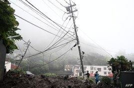 Rescue workers gather at the scene of a landslide following days of heavy rain in Atami in Shizuoka Prefecture on July 4, 2021…