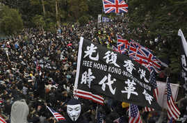 Participants wave British and U.S. flags during a rally demanding electoral democracy and call for boycott of the Chinese…