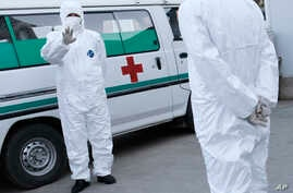 FILE - In this Oct. 27, 2014 photo, medical personnel in protective suits stand by an ambulance at the Sunan International…