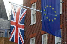 The European Union flag, right, and Britain's Union flag hang above the European Parliament Liaison Office in London, Tuesday,…