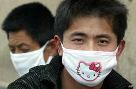 ** FILE ** In a file photo a man wears a Hello Kitty mask in Beijing, Wednesday, April 23, 2003. Thai police officers who break…