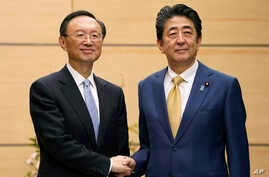 Yang Jiechi, left, politburo member of the Communist Party of China, meets Japanese Prime Minister Shinzo Abe at the latter's…
