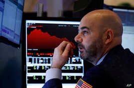 Trader Fred DeMarco works on the floor of the New York Stock Exchange, Friday, Feb. 28, 2020. Global stock markets are falling…