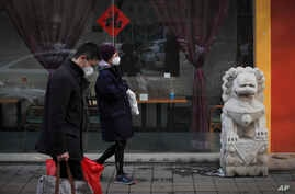 People wearing masks walk by a deserted restaurant during the Lantern Festival, the final day of the annual celebration of the…