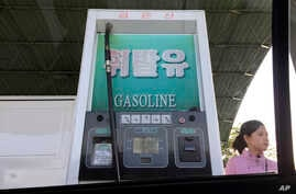FILE - In this April 26, 2017, file photo, a gas attendant waits by a pump at a gas station in Pyongyang, North Korea. While…