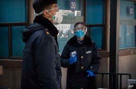 Security personnel wear protective face masks and goggles as they stand outside the entrance to the Beijing Railway Station in…