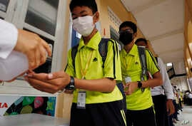 Students sanitize hands to avoid the contact of coronavirus before their morning class at a high school in Phnom Penh, Cambodia…