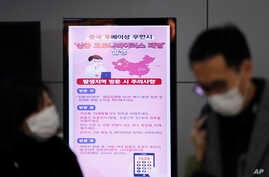 FILE - In this Jan. 27, 2020, file photo, a poster warning about coronavirus is seen as passengers wear masks in a departure…