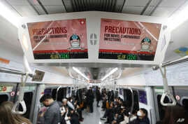 Electric screens about precautions against the illness COVID-19 are seen in a subway train in Seoul, South Korea, Monday, Feb…