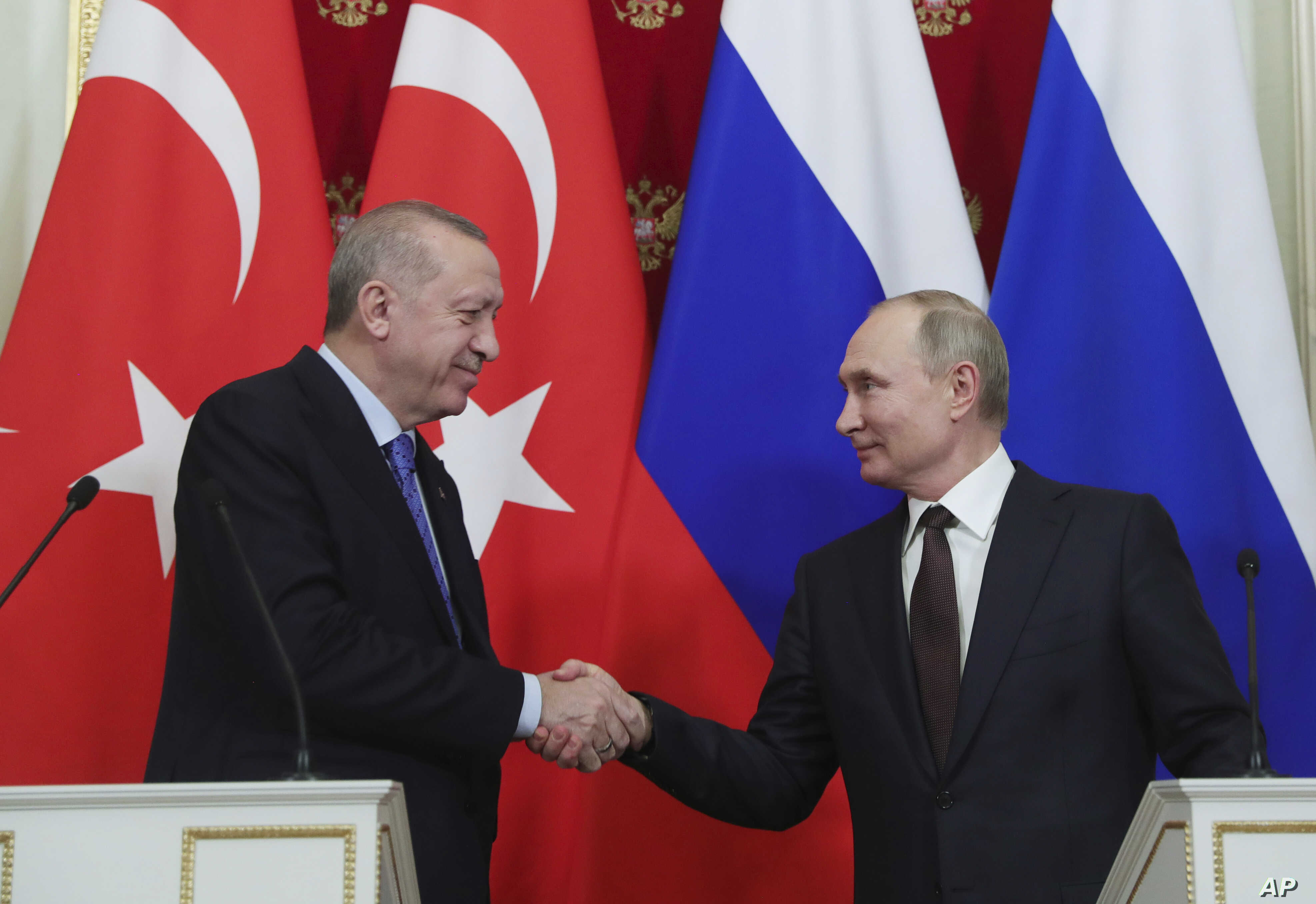 Russia's President Vladimir Putin, right, and Turkish President Recep Tayyip Erdogan shake hands after a joint news conference…