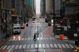 A commuter crosses 42nd Street in front of Grand Central Terminal during morning rush hour, Monday, March 23, 2020, in New York…