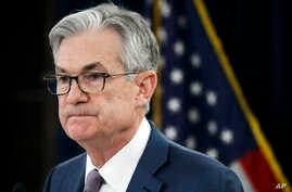 FILE - In this Tuesday, March 3, 2020 file photo, Federal Reserve Chair Jerome Powell pauses during a news conference to…