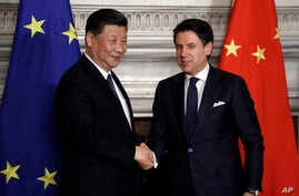 Chinese President Xi Jinping, left, and Italian Premier Giuseppe Conte shake their hands at the end of the signing ceremony of…