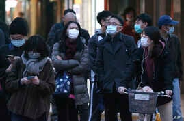 People wearing face masks as a precaution against the new coronavirus stand on a street in Taipei, Taiwan, Thursday, March 5,…
