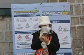 A woman wearing a face mask watches her smartphone in Seoul, South Korea, Saturday, March 21, 2020. For most people, the new…