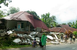 Residents stand near earthquake-damaged houses in Ambon, Maluku province, Indonesia, Friday, Sept. 27, 2019. Thursday's quake…