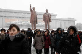 People leave after visiting the statues of their late leaders Kim Il Sung, left, and Kim Jong Il on Mansu Hill in Pyongyang,…