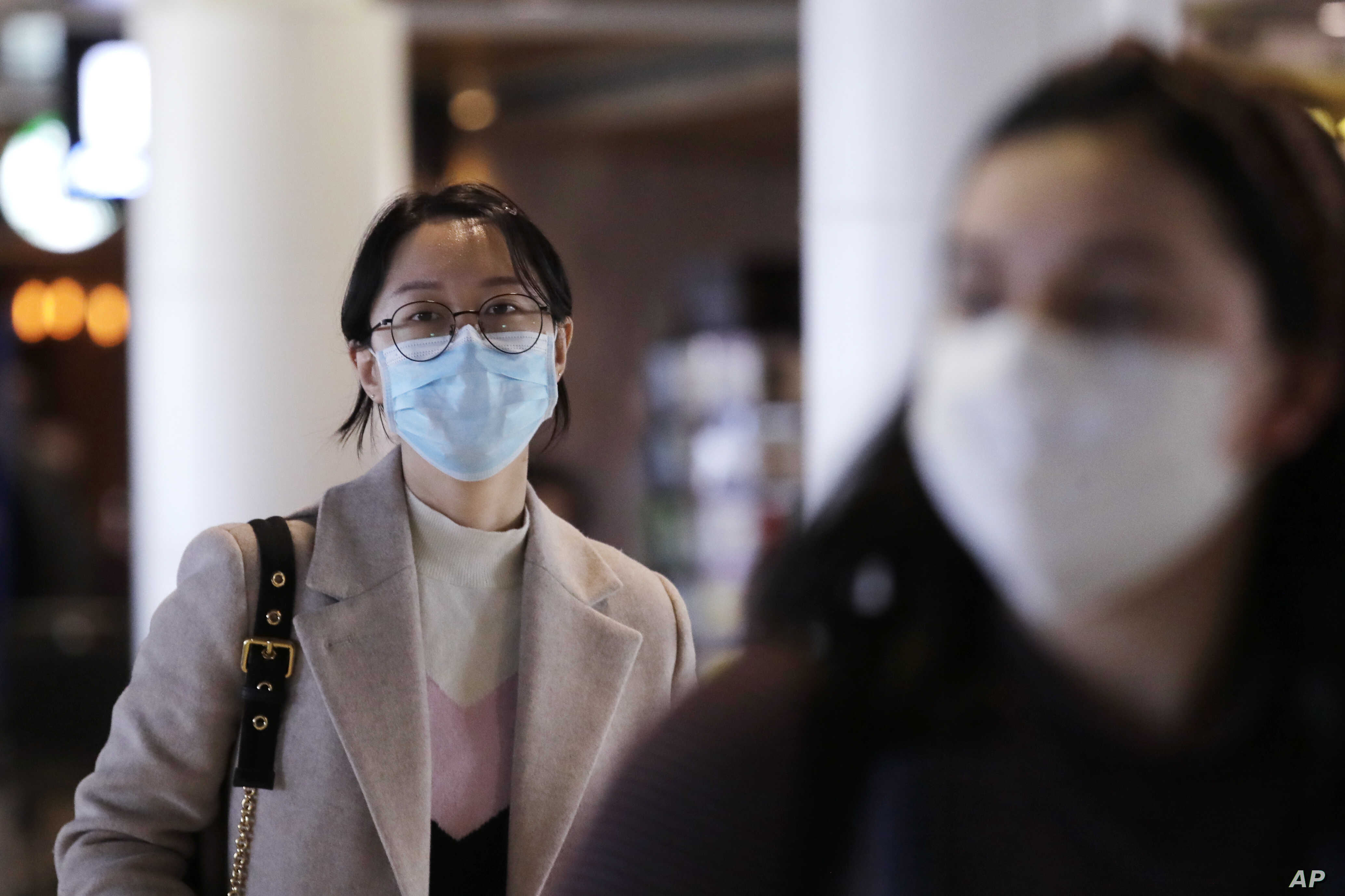 Travelers at Seattle-Tacoma International Airport wear masks Tuesday, March 3, 2020, in SeaTac, Wash. Six of the 18 Western…
