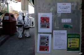 Workers wearing protective gears prepare to spray disinfectant near notices about precautions against new coronavirus in Seoul,…