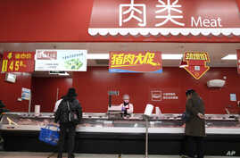 Shoppers buy meat at a supermarket in Beijing on Monday, March 16, 2020. China's consumer spending and factory activity fell…