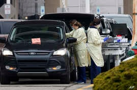 Healthcare workers screen a person seeking a coronavirus test at a COVID-19 drive-through testing site at Beaumont Hospital in…