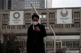 A man with a mask walks past the Tokyo Metropolitan Government building adorned with banners promoting the Tokyo 2020 Olympics…