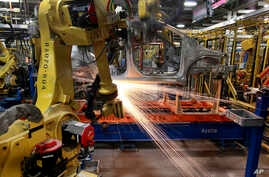 In this May 19, 2011 photo, robots weld a Chevrolet Sonic at the General Motors Orion Assembly plant in Orion Township, Mich…