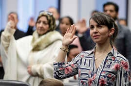 Anila Kadriu, from Albania, recites the Oath of Allegiance during a naturalization ceremony, Friday, Jan. 17, 2020, in…