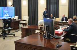 Russian President Vladimir Putin, right, attends a video conference with G20 leaders to discuss the coronavirus disease…