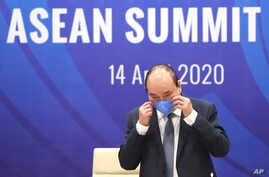 Vietnamese Prime Minister Nguyen Xuan Phuc prepares to remove his mask ahead of the special ASEAN summit on COVID-19 in Hanoi,…