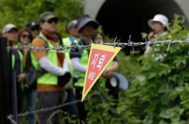 A sign indicating land mines is seen while hikers visit the DMZ Peace Trail in the demilitarized zone in Goseong, South Korea,…