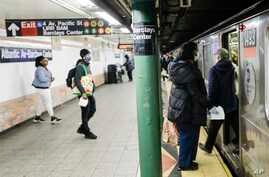 Patrons board a train while wearing masks at the Alantic Avenue station Tuesday, April 7, 2020, in the Brooklyn borough of New…